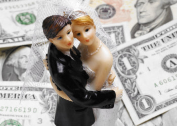 Bride and groom wedding figures standing on a pile of banknotes (Concept of the cost of weddings/prenuptial agreement)