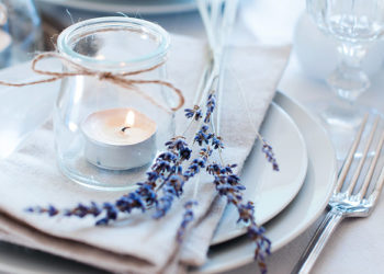 Dining table setting at Provence style, with candles, lavender, vintage crockery and cutlery, closeup.; Shutterstock ID 160531529